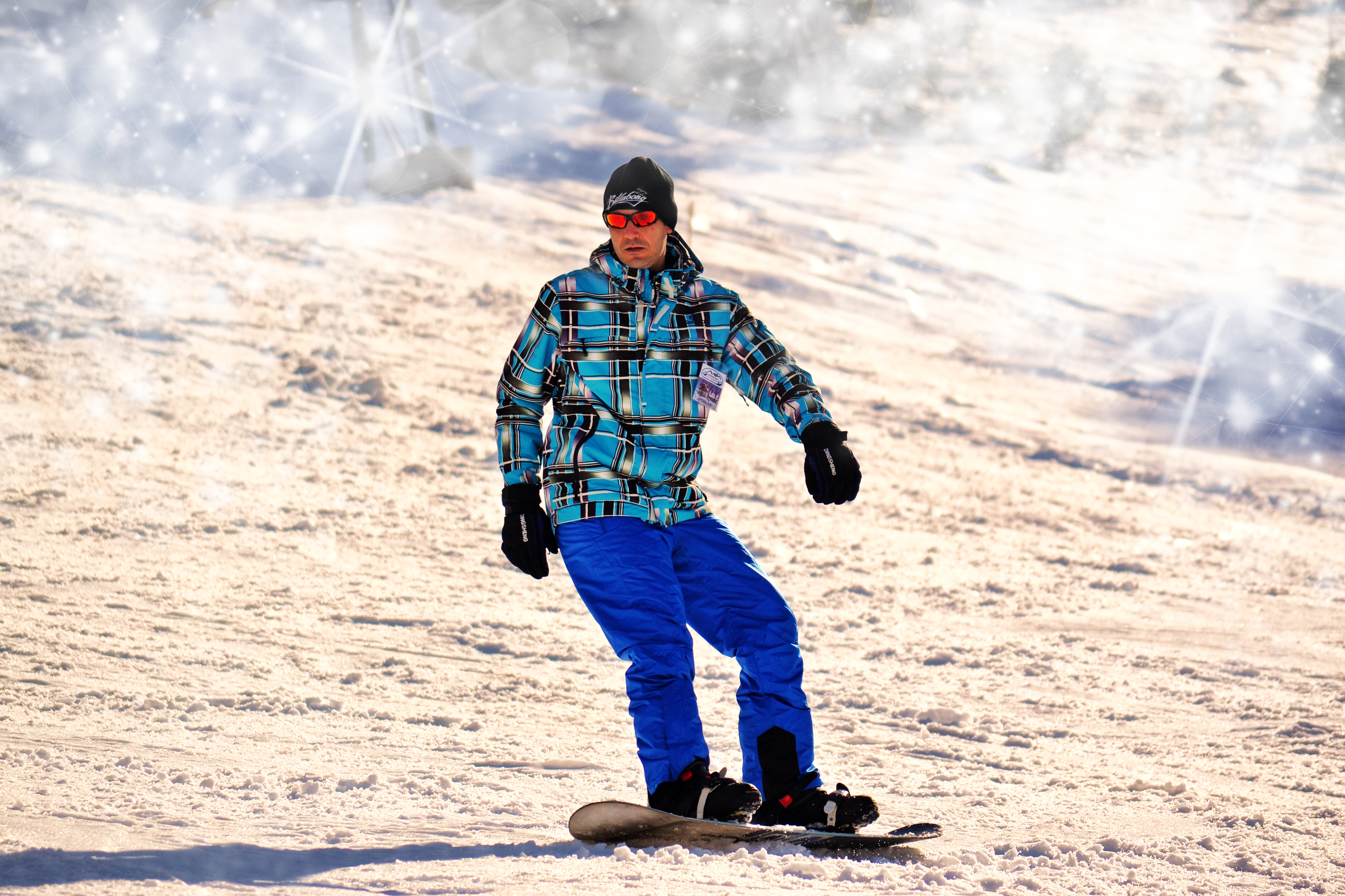 Relaxed snowboarder in orange goggles, blue trousers and fab multicoloured anorak