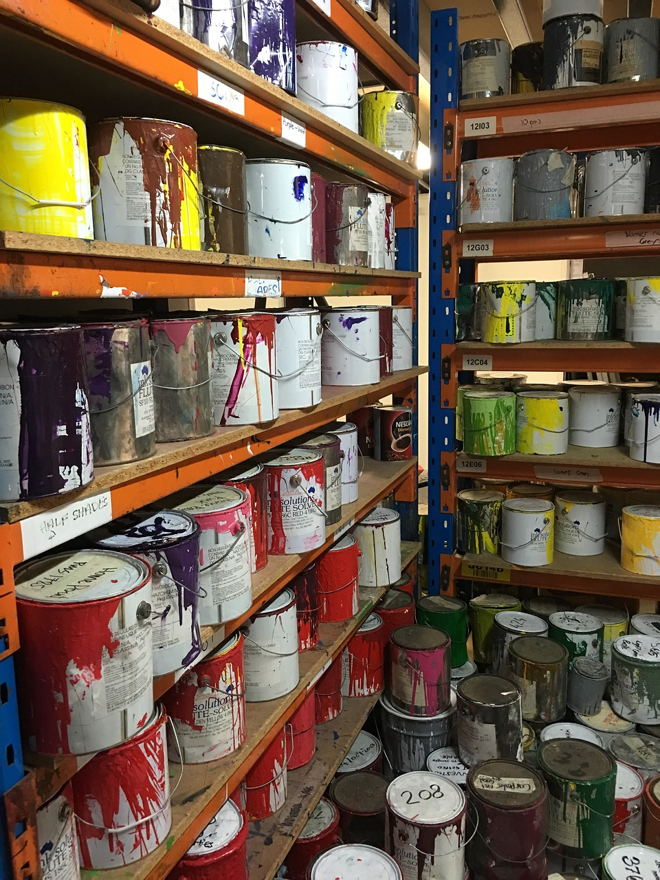 Partly used tins of paint on shelves, for reusing rather than recycling