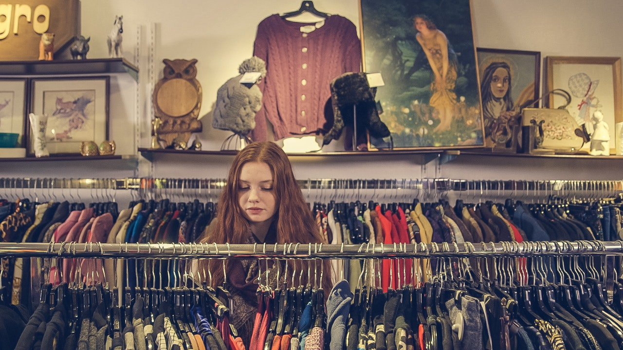 Young woman browsing in a charity shop - one way of recycling