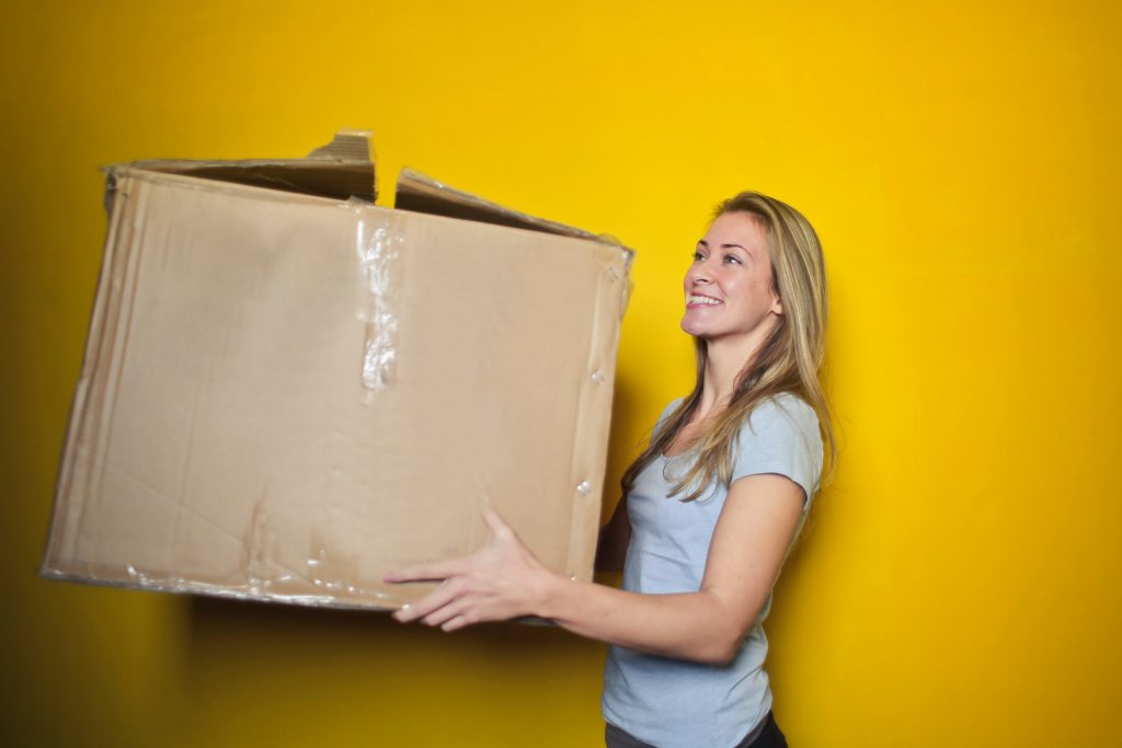 woman with large cardboard box. Organise your home