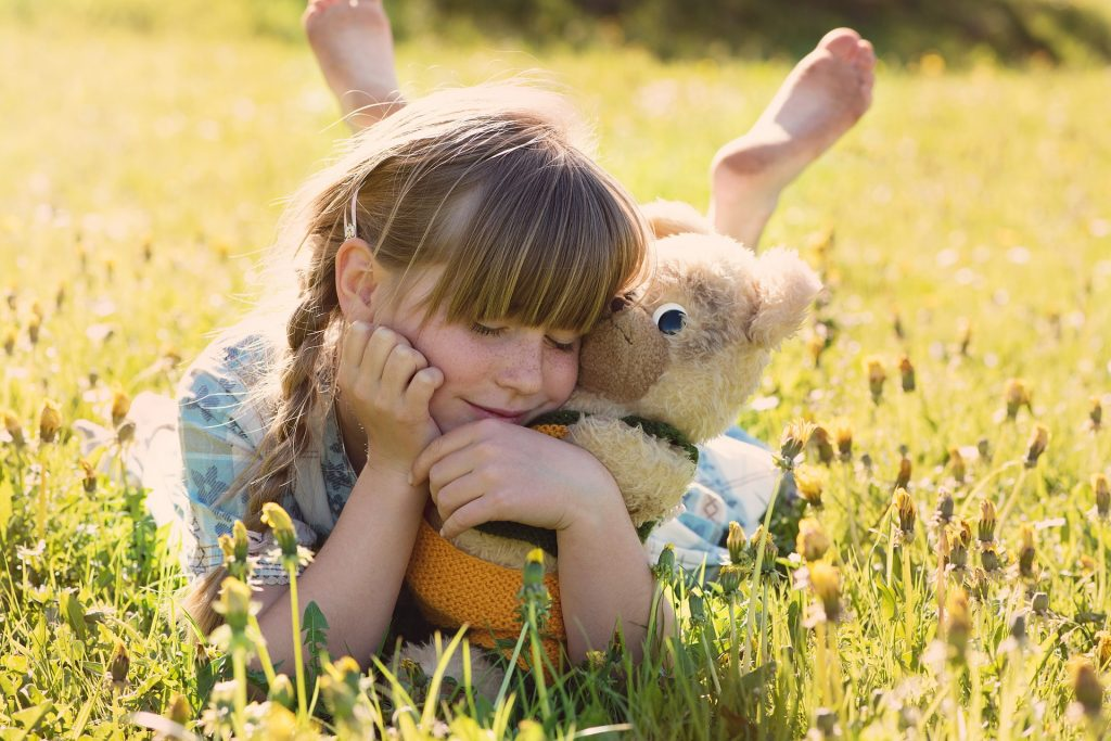 Girl lying on grass cuddling teddy bear. Joy. Decluttering