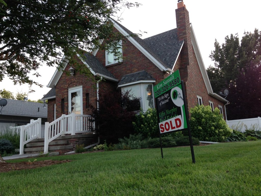 House with sold sign in lawn. Reasons to declutter before selling your house