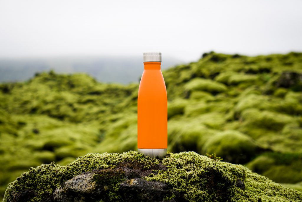 bright orange bottle on mossy rock. Why I love my job