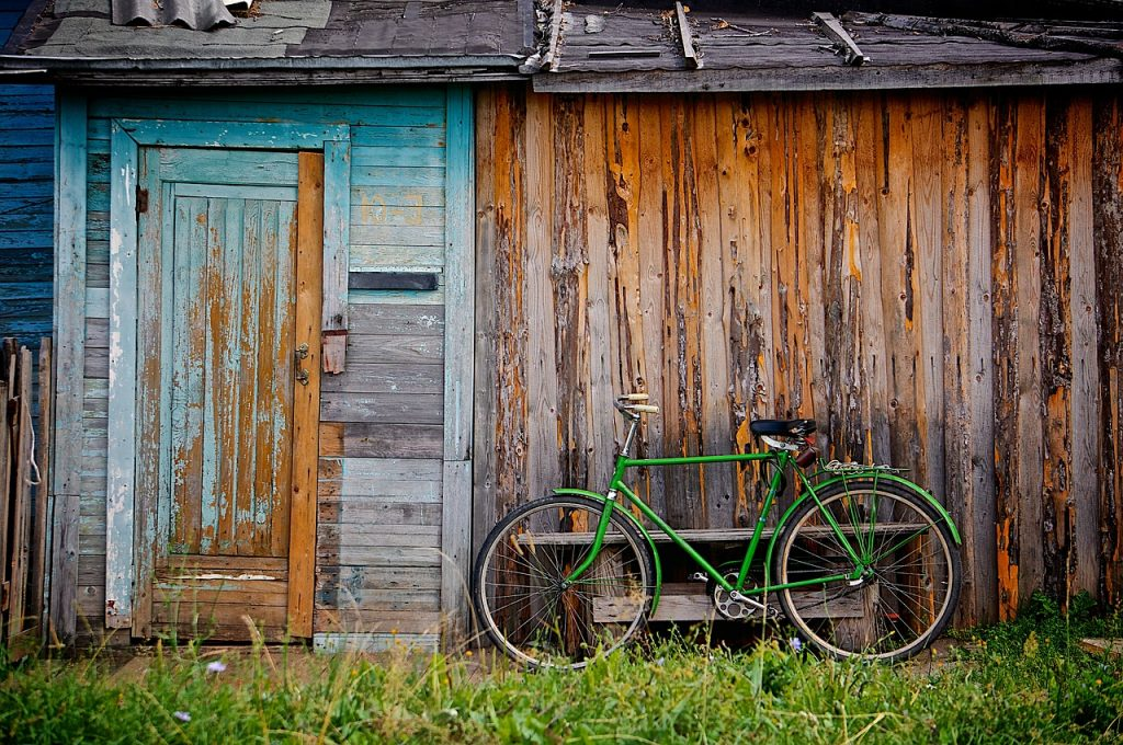 Green bicycle outside old shed. Sort out your garage or shed
