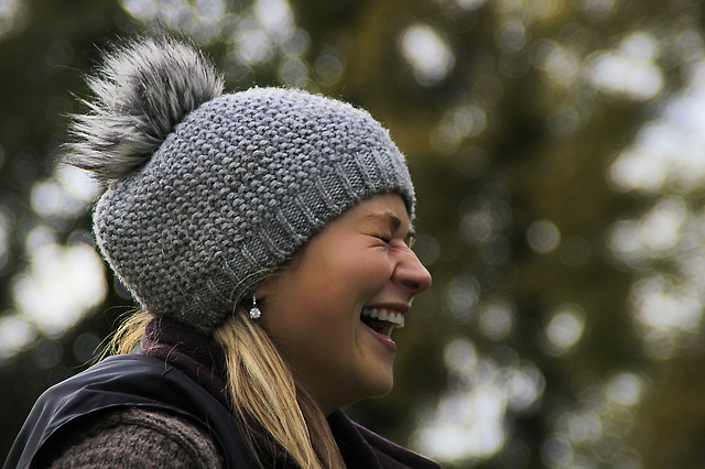 Woman laughing and wearing grey knitted bobble hat, gloves and scarves