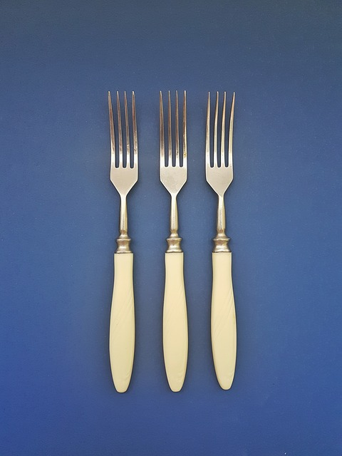 Three bone-handled forks on blue background. Declutter and simplify